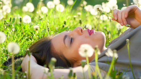 Beautiful Young Woman lying on the field in green grass and blowing dandelion. Outdoors. Enjoy Nature. Healthy Smiling Girl on spring lawn. Allergy free concept. 4K UHD video 3840X2160
