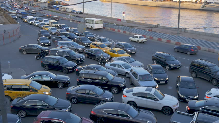 A traffic jam of cars. Impossible to move, cork. Time lapse. The city embankment. Sunset. The movement of cars along the road, and ships along the river. | Shutterstock HD Video #27024787