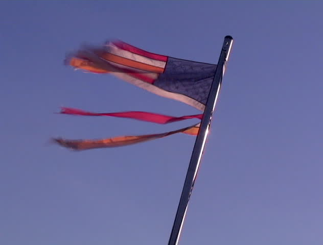 A tattered flag flaps in the wind on a clear blue day. Very disrespectful. DV NTSC video