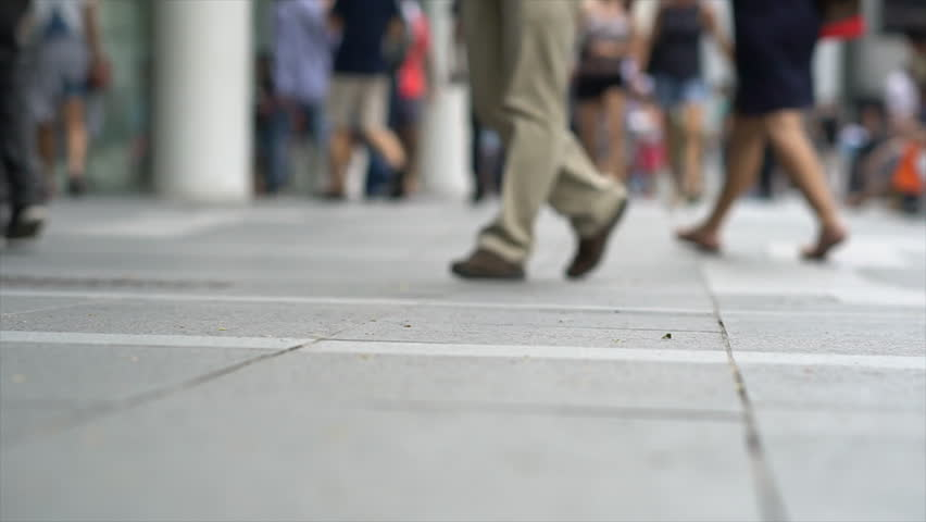 Timelapase 4K Crowds of people walk down a sidewalk in the Orchard Road district in Singapore.