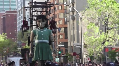 May 19-21, 2017: The little girl-giant walking toward the street of Montreal, Quebec, where she will meet her uncle.  The Giants were in Montreal to celebrate Montreal's 375th anniversary.