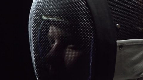 Tracking of professional fencer putting protective mask, tilting up head and looking up. Studio shot