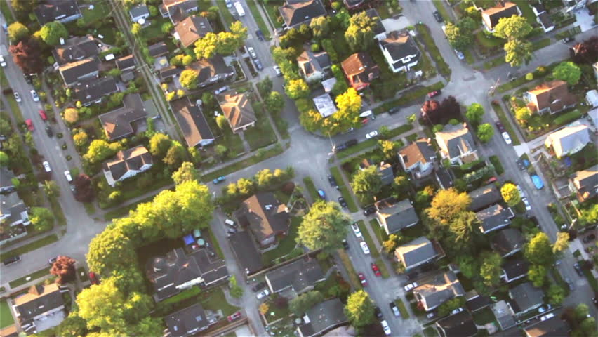 Overhead right pan across houses, yards and cars along suburban street