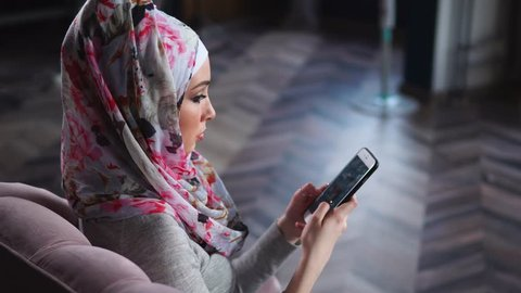 Young Muslim woman relaxing on the sofa at home and using cellphone to surf the internet. Lifestyle and leisure of modern Muslim women