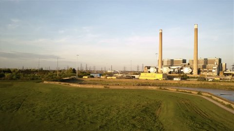 Tilbury Power Station, Essex; drone reveal establishing shot. Aerial video footage rising to reveal the decommissioned Tilbury Power Stations with electricity pylons disappearing behind.
