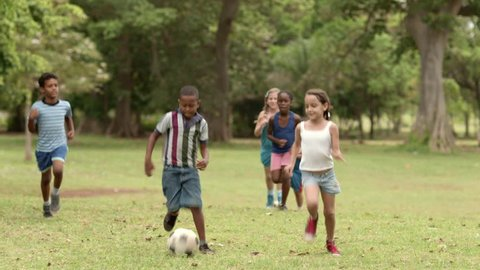 Multiethnic boys and girls playing european football, american soccer in city park. Summer camp fun