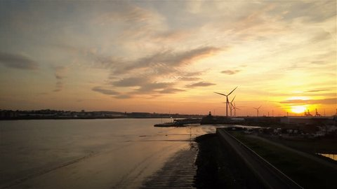 Aerial drone video footage of a dramatic sunset over the port of Tilbury, Essex, England, on the banks of the River Thames with wind turbines turning in the wind.