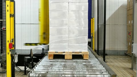 Boxes on a pallet wrapping with a foil by a heavy duty machine
