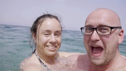Family middle-aged couple fooling around happily in the sea. Close-up bald man and his woman. Spend their holidays at the resort.