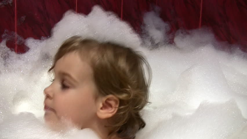little girl in bath with foam on head