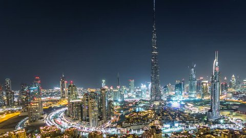 Dubai Downtown night timelapse with Burj Khalifa and other towers paniramic view from the top in Dubai, United Arab Emirates. Traffic on circle road and music fountain show. Pan right