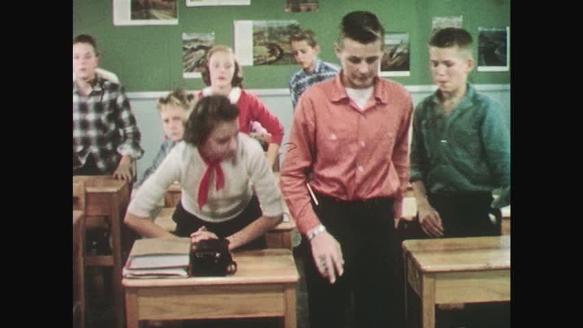 UNITED STATES: 1950s: teacher stands by board. Students pledge allegiance in classroom. Lady swears allegiance. | Shutterstock HD Video #27173947