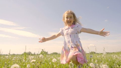 Cute little girl running in a meadow in the colors of a dandelion. Joyful cheerful child laughing outdoors. Summer sunny day. Slow Motion.