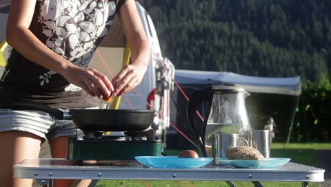 Part #2. Woman cooking breakfast in camping. Female hands breaking eggs to frying pan, salt and cover with a lid