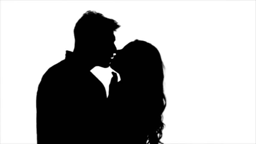 loving couple look at each other and begin to kiss silhouette white background