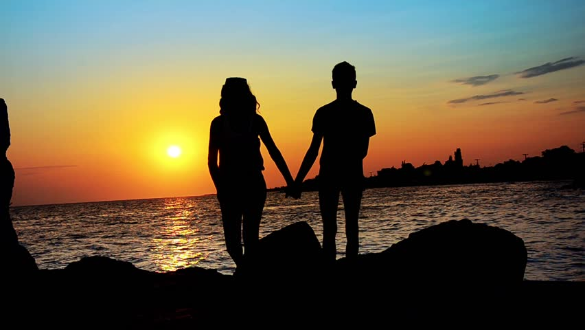 Teenage couple holding hands in the sunset