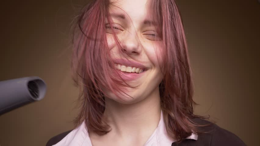 Emotional happy teenager girl make funny faces while drying her hair. Slow motion