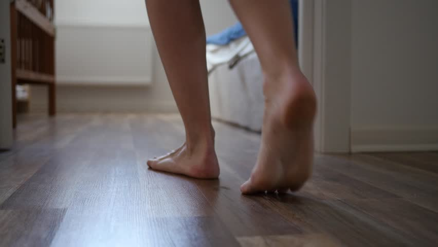 Barefoot woman walks into room stepping onto a laminate legs camera slow motion