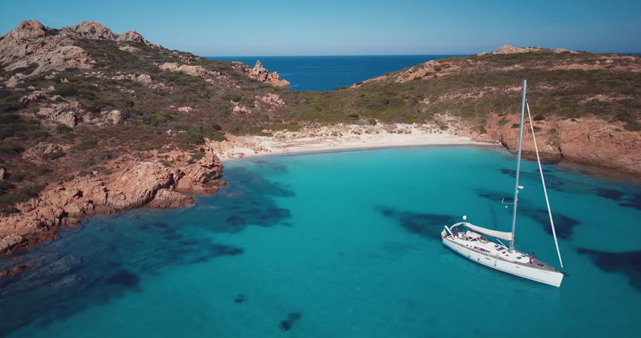 Video from above. Aerial view of a boat in front of the Mortorio island in Sardinia. Amazing beach with a turquoise and transparent sea. Emerald Coast, Sardinia, Italy.