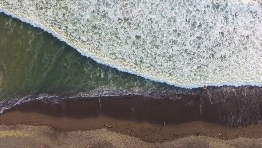 Aerial top view of ocean waves and foam washing up onto beach. Zoom in shot made with drone | Shutterstock HD Video #27297928