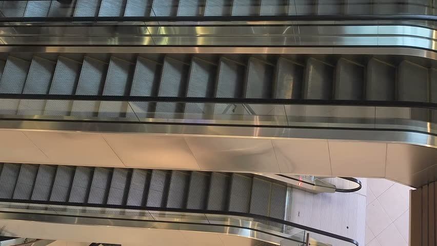 moving staircase with people running up and down modern escalator stairs which moves indoors
