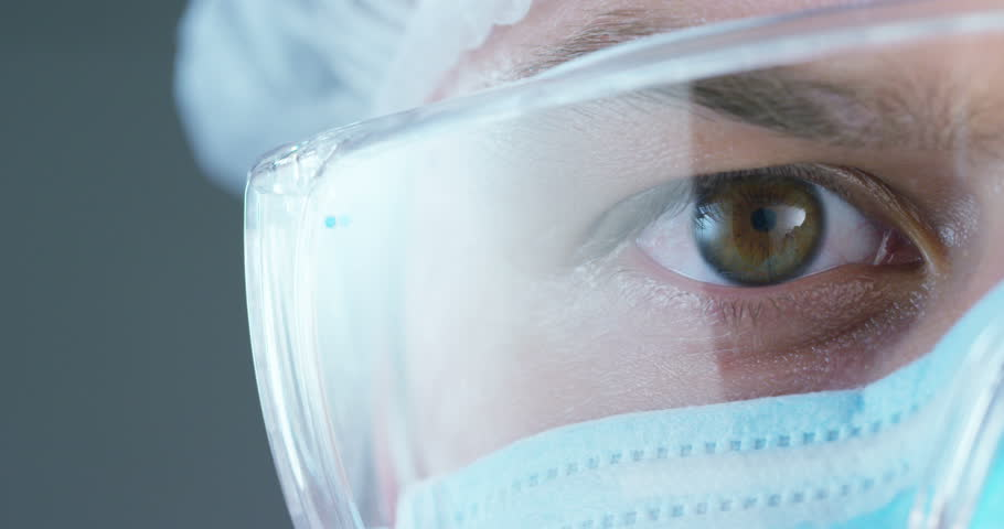 A doctor or surgeon in a medical mask, a respirator, brown eyes, goggles, a surgical cap, in a hospital or a clinic. Concept: the first medical help, help treat people, surgery, doctors, health. | Shutterstock HD Video #27322282