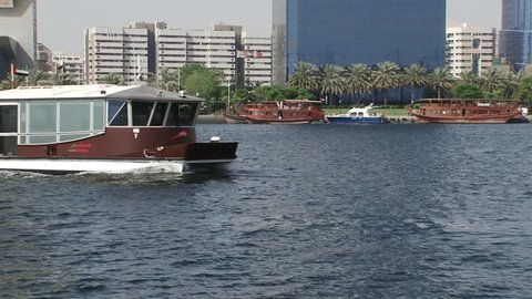DUBAI, UAE - CIRCA 2008: Pan-right shot of Dubai water bus crossing the Creek with buildings in the background. Dubai's saltwater creek has always been one of the main arteries of transport.