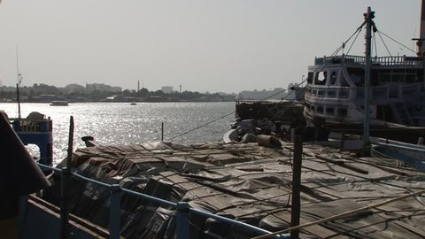 DUBAI, UAE - CIRCA 2008: Pan-left across the Dhow Wharfage area on the banks of Dubai Creek north of Maktoum Bridge. Hundreds of traditional dhows are docked waiting to load and unload diverse cargo.