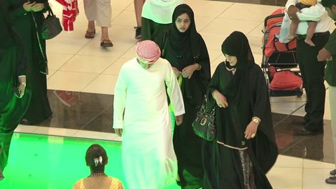 """UAE - CIRCA 2008: Tilt-down shot of veiled women with Emirati man in a mall. The man is wearing a """"thobe"""" a """"igal"""" the black head rope holding the """"ghutra"""" which is the red and white headcloth."""