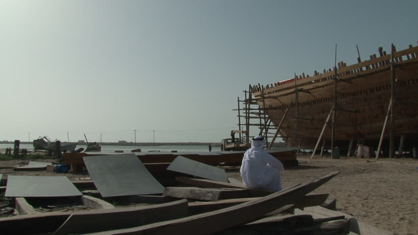 UAE - CIRCA 2008: Pan-right shot of an Emirati man sitting in a traditional ship building yard on the seashore looking at a a dhow being constructed.
