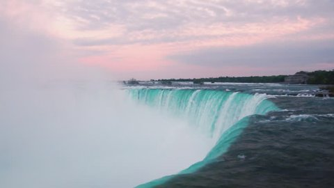 Niagara falls at sunset with a lot of mist and clouds