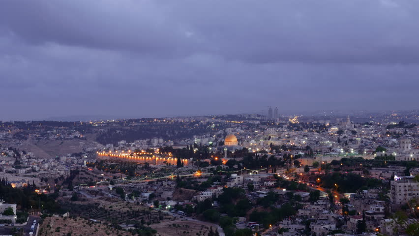 Night falls on Jerusalem city. Citylights light up at night while sunset goes over Jerusalem Dome of the Rock and Al Aqsa mosque timelapse.