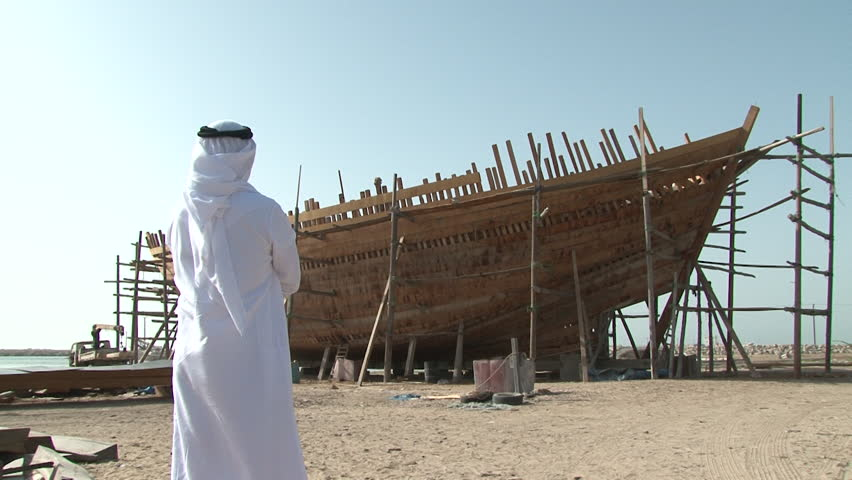 UAE - CIRCA 2008: Static shot of a man in traditional Emirati dress seen from behind walking towards boat construction on the sandy shore.