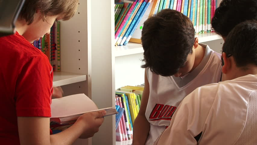 DUBAI, UAE - CIRCA 2013: CU schoolboys in a library. Illiteracy is a big issue in the Arab world with 33% not able to read or write. However, six Arab countries rank above the world average of 76.5%.