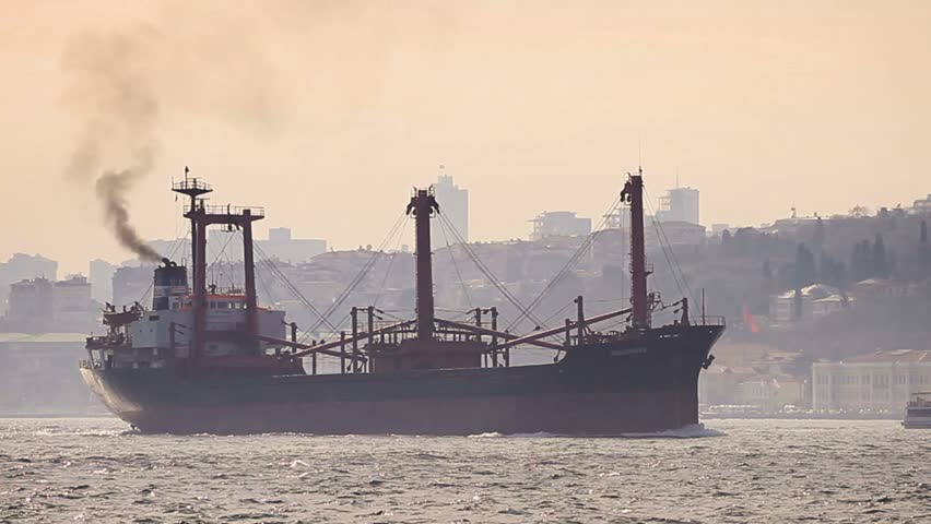 Marine air pollution. Istanbul in smog with a cargo ship