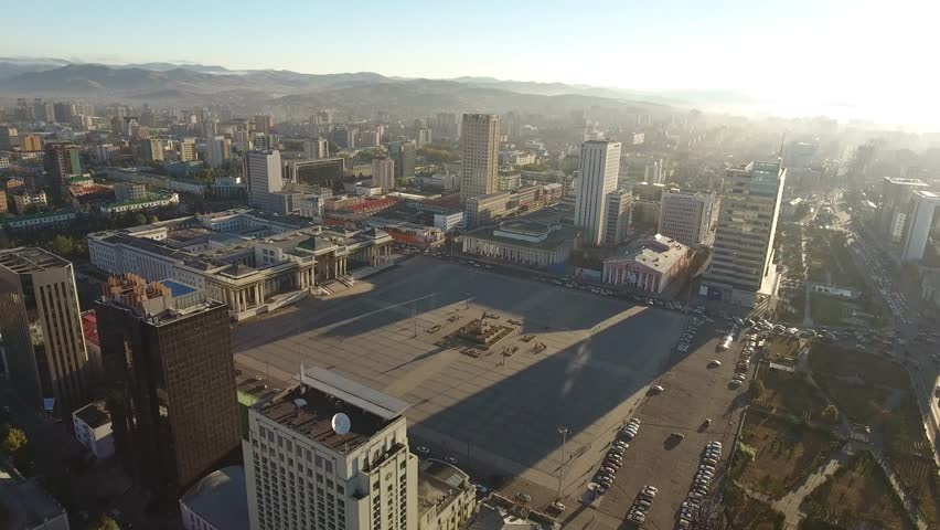 Grand Sükhbaatar central capital Ulaanbaatar Square. Colonnade Mongolia Palace megalopolis. Morning sun warm sunrise long shadows. Aerial helicopter flight around