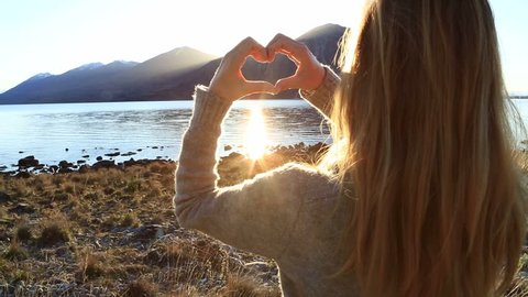 Young attractive caucasian woman makes heart shape frame with fingers by the lake in New Zealand. Young female framing sunrise. Sun is rising behind mountain lake