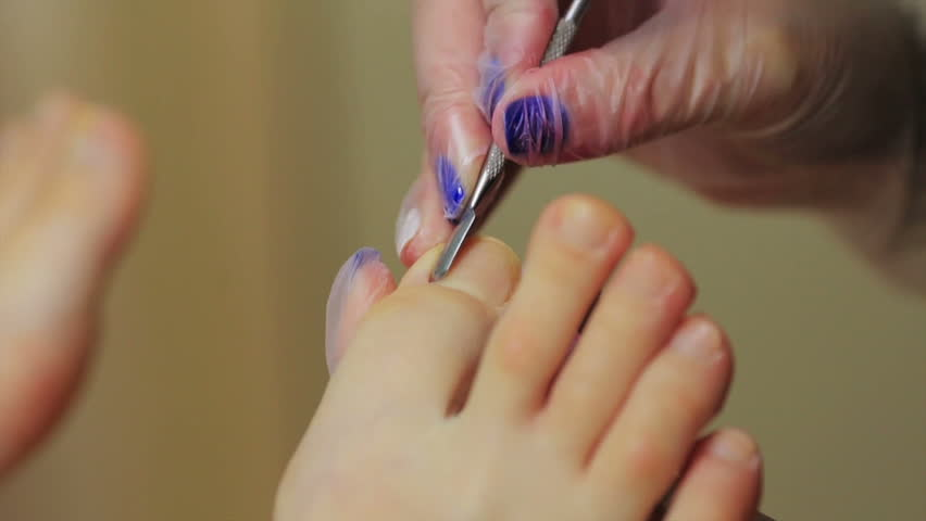 Caring about the girl legs pedicure, polish, beautiful lights. Pedicures in the salon. The master cares for the nails and feet of the client, doing the pedicure. Peeling feet pedicure procedure.   Shutterstock HD Video #27439588