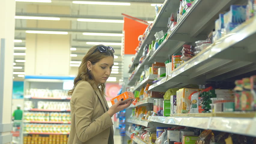 Beautiful woman shopping in supermarket and deciding what to buy. | Shutterstock HD Video #27444382