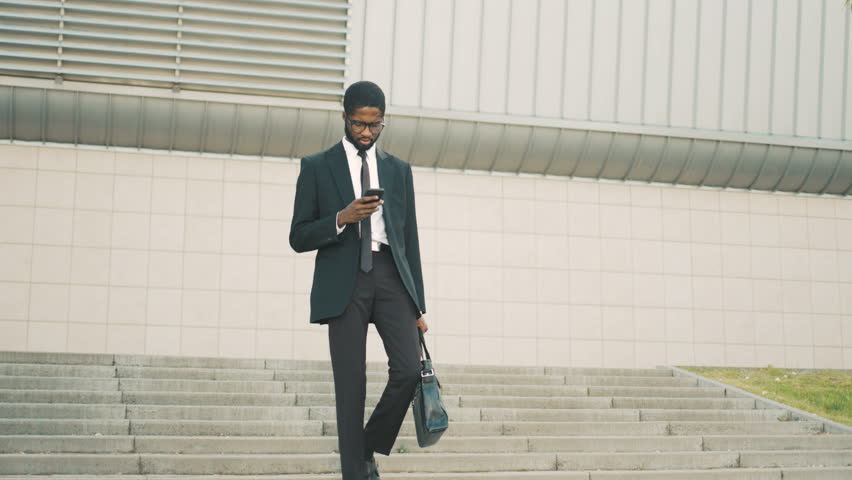 Attractive black african american businessman walking down the stairs, steps, using smart phone. Man reading sms, surfing internet #27449308