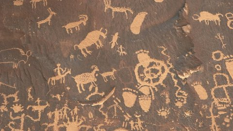 zoom in shot on a drawing of a human figure on horseback hunting sheep at newspaper rock in canyonlands national park, utah