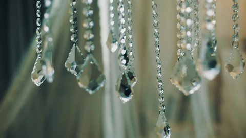 Chandelier glass faceted pendants particles in front of bright white light in photo studio, close up