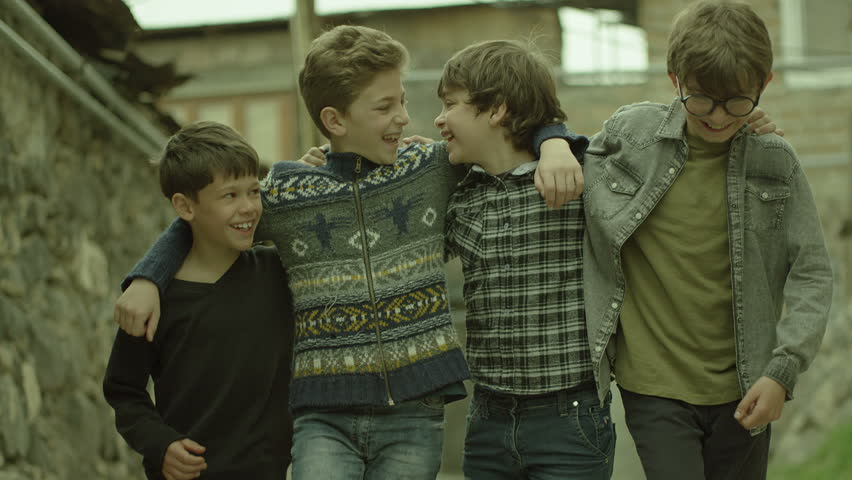 Childhood Memories.  View of a group of teen friends enjoying a walk, hugging each other. Vintage times. Childhood Memories. Shot on RED EPIC DRAGON Cinema Camera in slow motion.