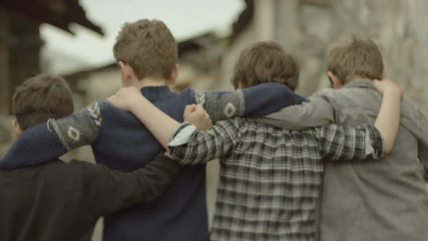 Childhood Memories.  Back view of a group of teen friends enjoying a walk, hugging each other. Vintage times. Childhood Memories. Shot on RED EPIC DRAGON Cinema Camera in slow motion.
