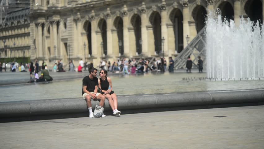 PARIS, FRANCE - MAY 23, 2017: Young couple romantic kissing near fountain and Museum Louvre in city Paris