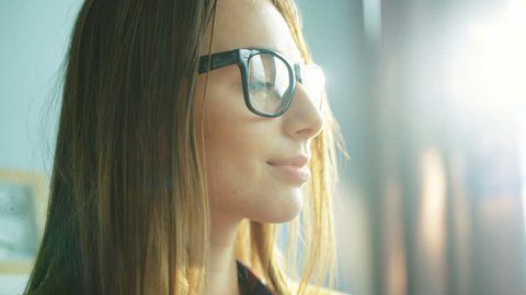 Close up woman face portrait. Woman wearing glasses, drinking coffe and looking straight at the camera, smiling. Sun rays. Close up