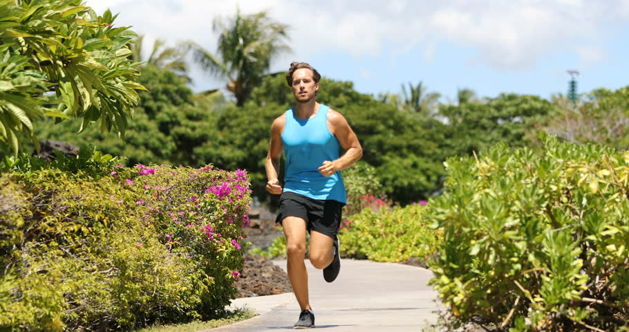 Runner man running on park path exercising on beautiful summer day. Fit male fitness model training doing recreational jogging workout. SLOW MOTION