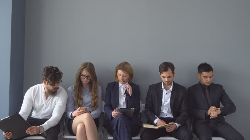 Unemployed expect interviews sitting on chairs in the hallway of an office building. | Shutterstock HD Video #27661918