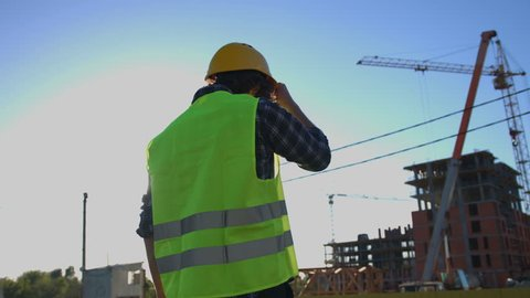 Back view of architect with black curly hair in shirt and green vest looking on construction process, putting on head the helmet on unfinished construction background.