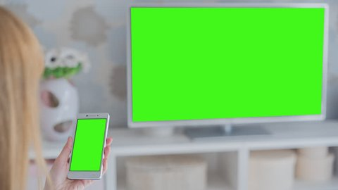 Young woman sitting on couch in front of the TV holds SmartPhone with pre-keyed green screen. Perfect for screen compositing. 10bit ProRes 444